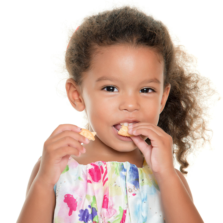 42288522 – cute small girl eating a cookie isolated on white