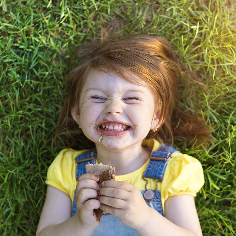44727078 - cute little girl with chocolate face lying on a grass